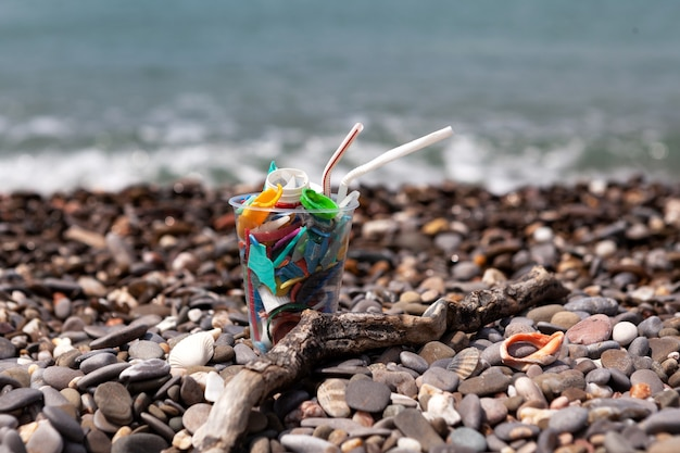 Gobelet en plastique jetable avec des déchets en plastique au bord de la merles problèmes écologiques menacent la mer