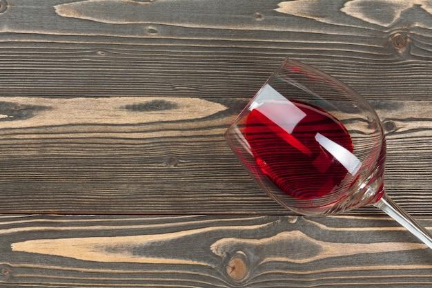 Gobelet de vin rouge sur une table en bois sur fond de mur en bois