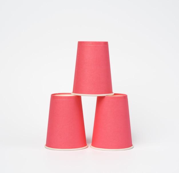 Gobelets jetables en papier rose sur fond blanc, concept écologique, zéro déchet