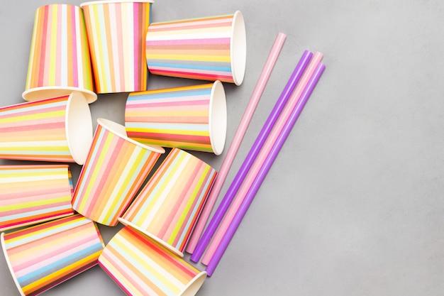 Gobelets en papier colorés et pailles en plastique colorées pour les boissons. mise à plat