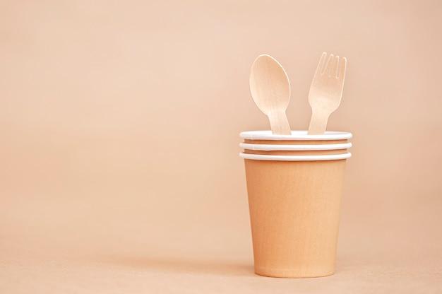 Gobelets en papier jetables avec fourchette et cuillère en bois sur fond de papier