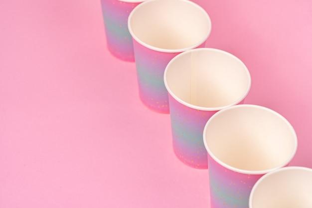 Gobelets en papier jetables roses d'affilée sur fond rose