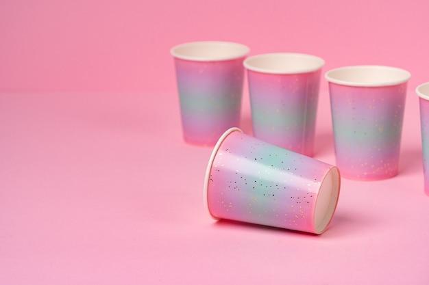 Gobelets en papier jetables roses d'affilée sur rose