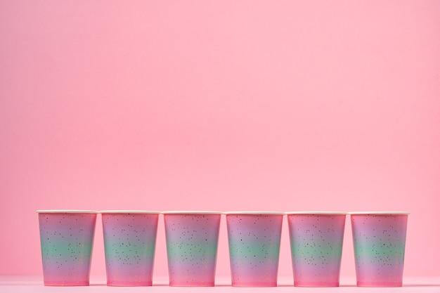 Gobelets en papier jetables roses d'affilée sur table rose