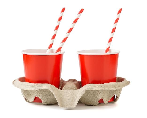 Gobelets en papier jetables rouges avec un porte-gobelet et des pailles. isolé sur un blanc.