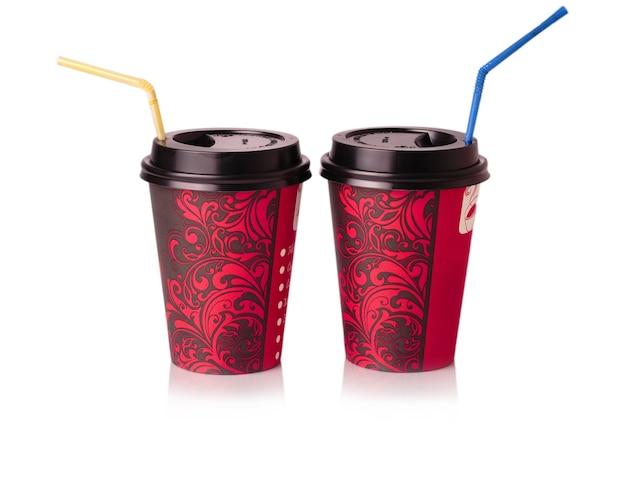 Gobelets en papier rouge à boire avec de la paille sur une surface blanche