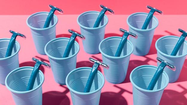 Gobelets en plastique bleu haute vue et lames de rasoir bleues