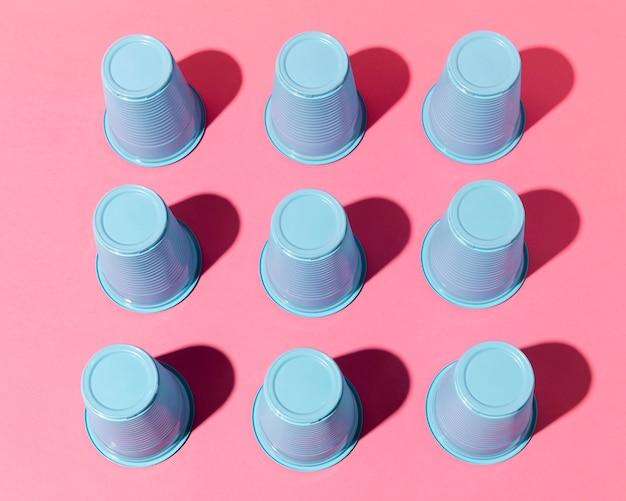 Gobelets en plastique bleu haute vue avec des ombres