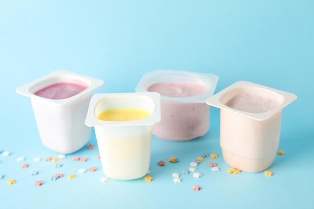 Gobelets en plastique avec du yaourt et de petites étoiles sur fond de couleur,