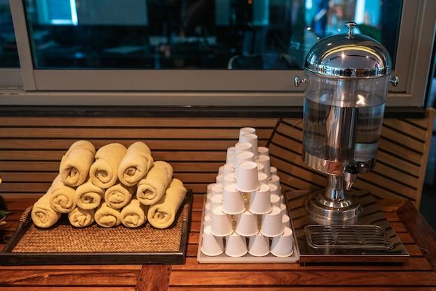 Gobelets en plastique et refroidisseur d'eau, pile de serviettes propres dans une salle de sport moderne