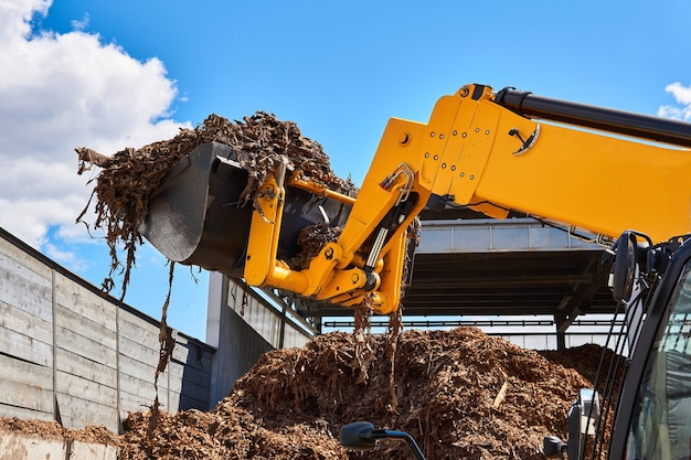 Godet chargeur chargeant l'écorce de bois dans une industrie du bois