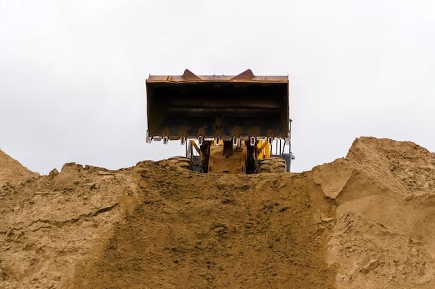 Le godet du chargeur vient de décharger le sable sur le tas de sable