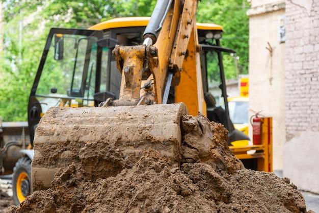 Le godet d'excavatrice verse le sol