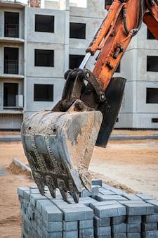 Un godet de mini-pelle repose sur une palette de dalles de pavage sur un chantier de construction. matériel de construction compact pour terrassement et aménagement paysager.
