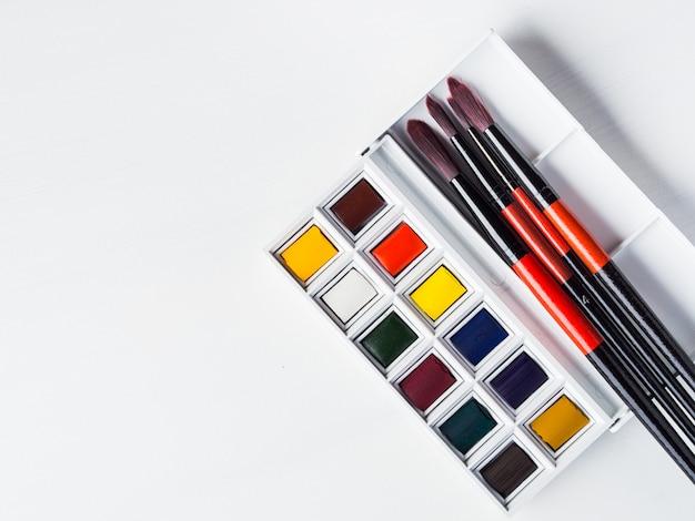 Godets et pinceaux aquarelles sur blanc