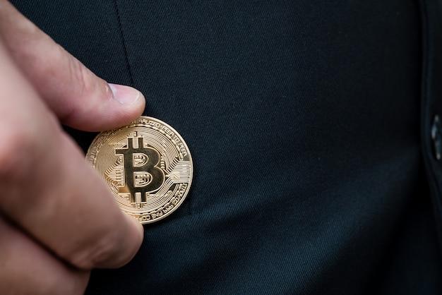 Golden bitcoin dans une main d'homme, digitall symbole d'une nouvelle monnaie virtuelle.