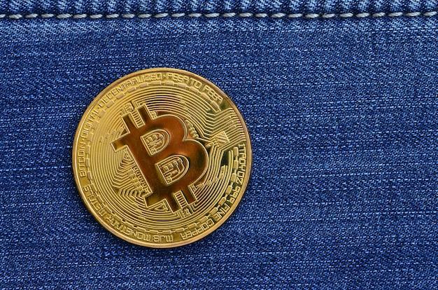 Golden bitcoin repose sur un tissu de jeans. nouvelle monnaie virtuelle. nouvelle monnaie crypto sous forme de pièces