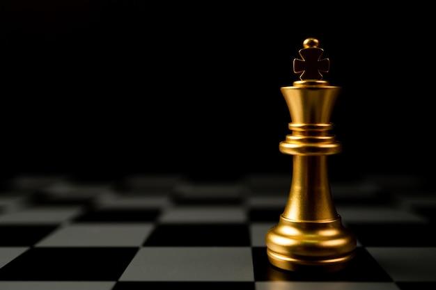 Golden chess king debout seul sur l'échiquier