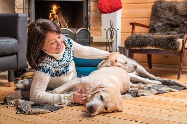 Golden labrador retrievers se trouvent avec une femme asiatique d'âge moyen sur une couverture devant la cheminée d'une maison de campagne.
