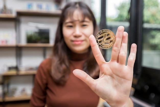 Golden litecoin (crypto-monnaie) en main de femme d'affaires.