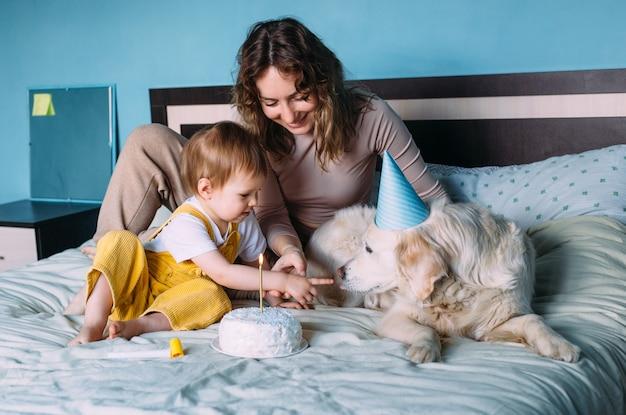 Golden retriever du labrador avec un petit enfant fête son anniversaire avec un gâteau