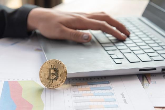 Goleden bitcoin se tient à côté de labtop dans la salle de bureau