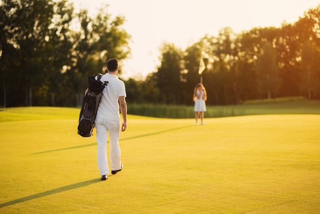 Golfers walks by course family recreation.