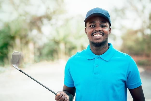 Golfeur africain debout dans un parcours de golf