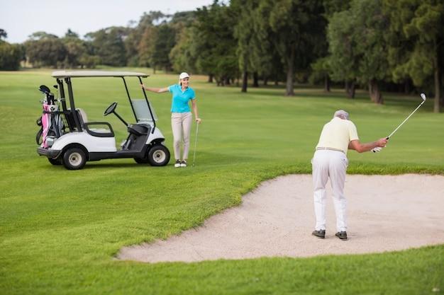 Golfeur, debout, sable, piège, femme