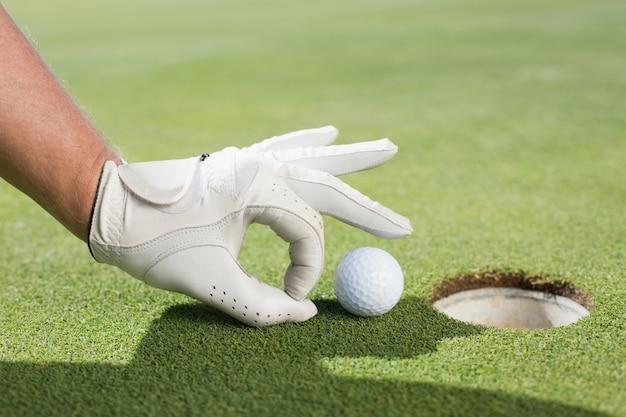 Golfeur essayant de balancer la balle dans le trou
