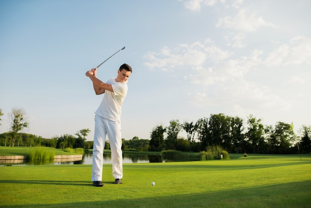 Le golfeur est en train de prendre des photos de swing shot sur un lac magnifique.