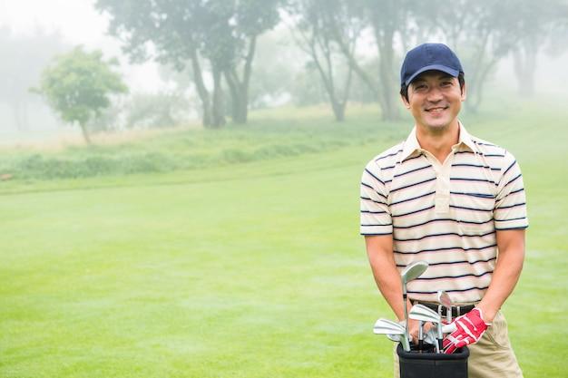 Golfeur joyeux, souriant à la caméra tenant le sac de golf