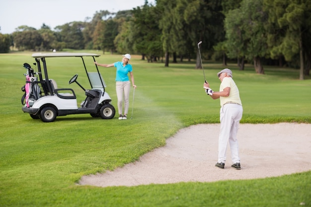Golfeur mature jouant sur un piège à sable par femme