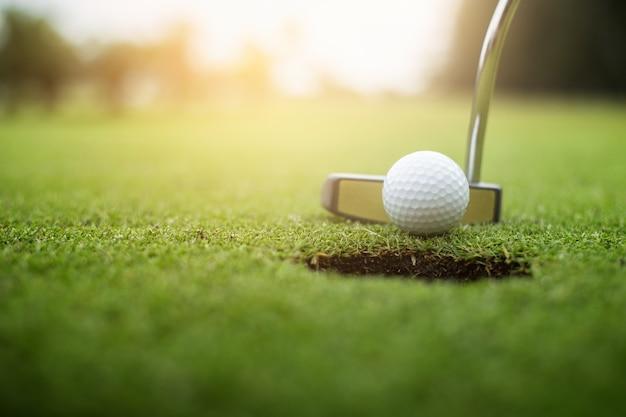 Golfeur mettant la balle de golf approche du trou de golf sur le golf vert