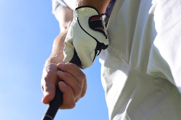 Golfeur portant un golf tenant un putter.
