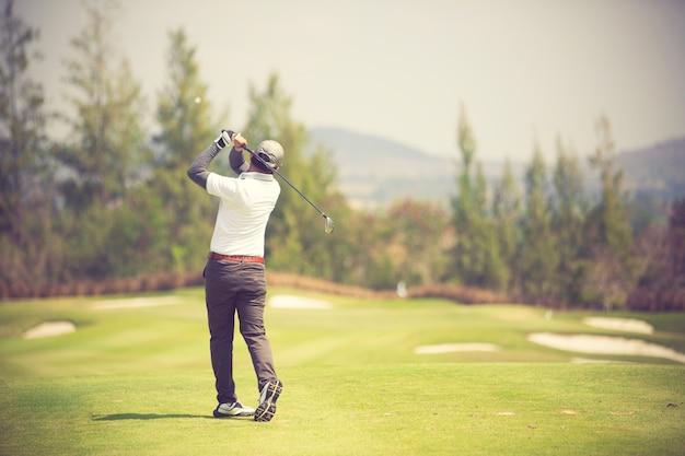 Les golfeurs frappent le parcours de golf dans la couleur vintage de l'été