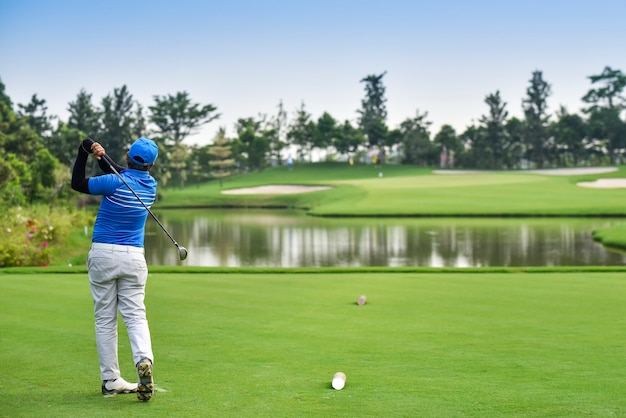 Les golfeurs frappent le parcours de golf depuis le fairway au lever du soleil