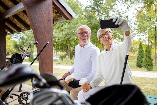 Golfeurs seniors professionnels prenant selfie avant de jouer au golf pour les réseaux sociaux.
