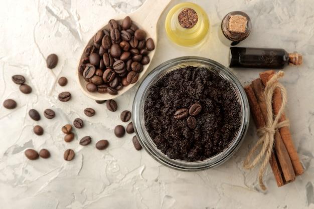 Gommage au café maison dans un bocal pour le visage et le corps, et divers ingrédients pour faire un gommage sur fond clair. spa. produits de beauté. soins cosmétiques. vue d'en-haut