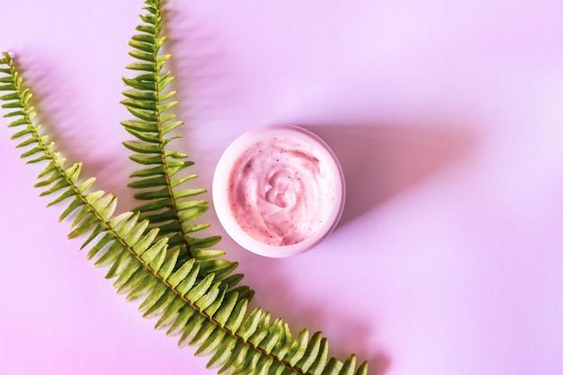 Gommage aux fraises roses et feuilles de fougère sur fond lilas brillant. concept de beauté et spa de soins de la peau.