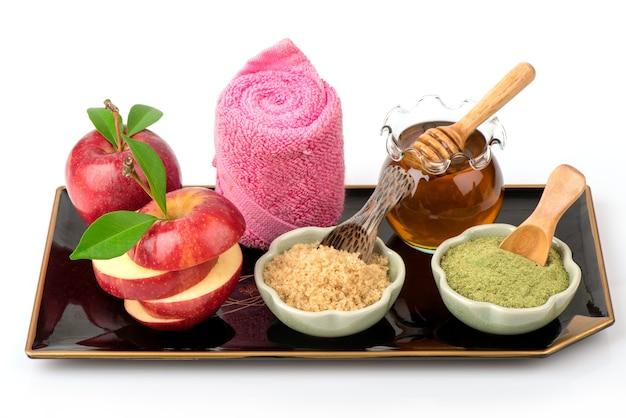 Gommage aux pommes, cassonade, thé vert et miel isolé sur fond blanc.