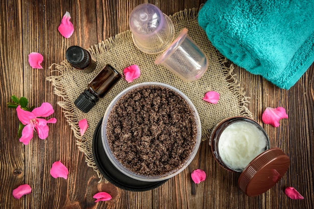 Gommage corporel au café, sucre et huile de noix de coco, huiles essentielles, bocaux sous vide de massage sur une table rustique en bois foncé avec des fleurs roses.