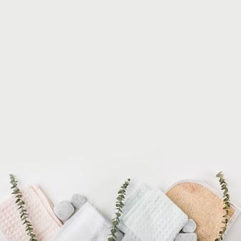 Gommage corporel au luffa; serviette en coton et pierres de spa avec des brindilles sur fond blanc