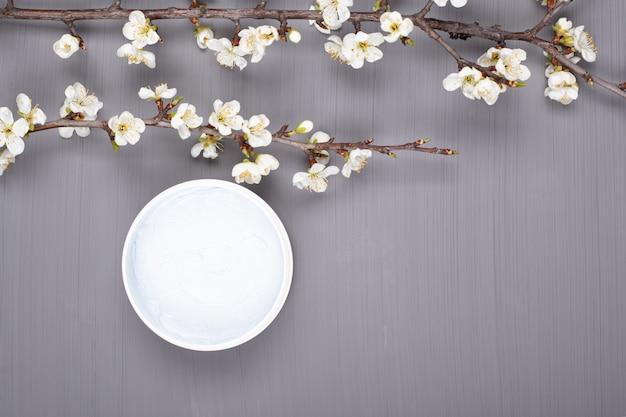 Gommage corporel sur fond gris avec des branches de fleurs de cerisier blanc vue de dessus copie espace