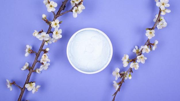 Gommage corporel sur fond violet avec des branches de fleurs blanches vue de dessus. beauté, soins de la peau, spa.