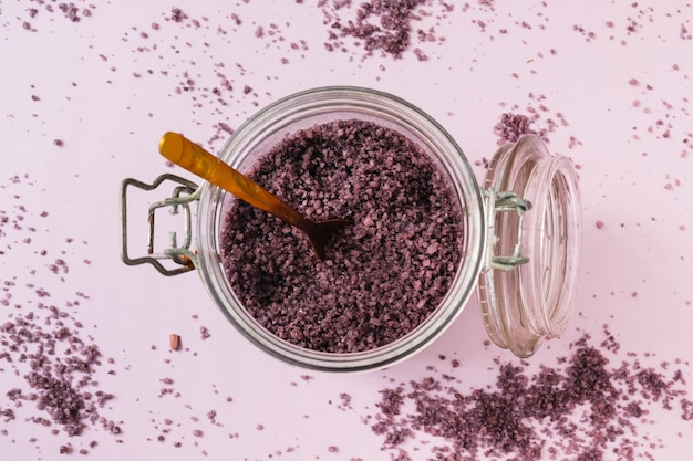 Gommage naturel dans un verre ouvert avec une cuillère en bois sur fond rose