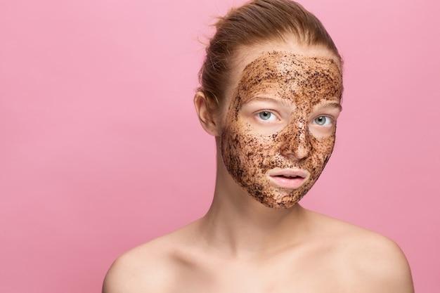 Gommage de la peau du visage. portrait de sexy modèle féminin souriant application de masque de café naturel, gommage du visage sur la peau du visage.