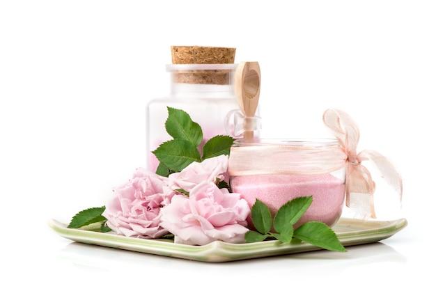 Gommage de la peau à la rose de damas extraite et au sel de mer isolé sur blanc.