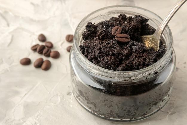 Gommage visage et corps au café fait maison dans un bocal en verre avec une cuillère sur fond clair. soins cosmétiques.