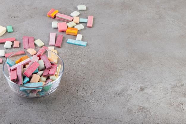 Gommes colorées dans des bols en verre sur surface grise